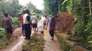 Warga membersihkan tanah yang menutupi jalan desa. (Wid)